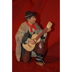 Uomo in ginocchio con chitarra
